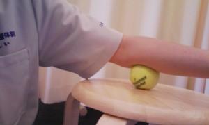 肘の周りの筋肉のトリガーポイントをボールを使ってほぐす